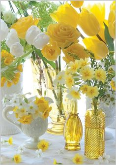 Table décor for Easter: Yellow tulips, roses, pansies, etc, white tulips and apple blossoms (showcased in yellow and white vases and white creamer pitcher). <> (Easter, holiday, spring)