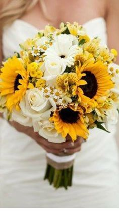 A bride holds a pretty wedding bouquet consisting of sunflowers, daisies and roses.