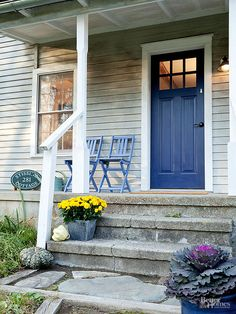 Displaying a single color in different ways in varying tones creates pleasingly pulled together spaces. Cobalt blue paint turns this front door into a focal point, while periwinkle chairs, bluish flagstones, and worn and shiny blue flowerpots provide finishing touches that result in a captivatingly well-rounded composition.