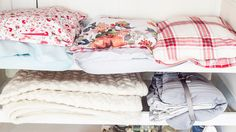 Colourful bed linen stored in pillow cases and folded blankets   Quick and easy laundry tips and hacks   Tesco Living