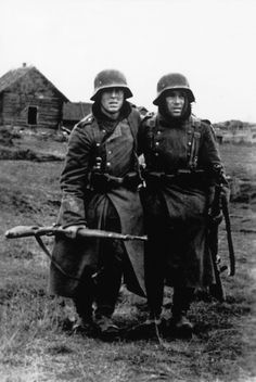 Two Wehrmacht soldiers carrying their K98 Mauser rifles.
