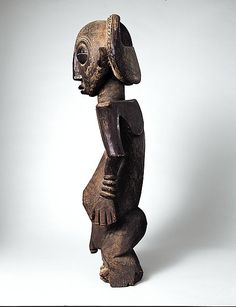 Boyo, DRC. Ancestor Figure: Male. C 18-19 - Boyo communities within the Democratic Republic of Congo are renowned for their series of majestic royal ancestral representations. This figure is said to memorialize Akessa, grandson of a chief who migrated north to the current location of the Boyo peoples. It is a classic example of Boyo commemorative representations in which distinguished leaders are depicted simultaneously as serenely introspective and as an awesome, otherworldly physical…