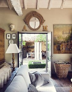 I Love the french doors looking out to pond and outdoor kitchen and eating area nterior Design | Spanish Stone House - DustJacket Attic