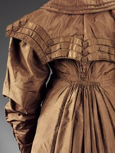 Coat of brown silk taffeta. C. 1818. False buttons covered with gauged fabric.