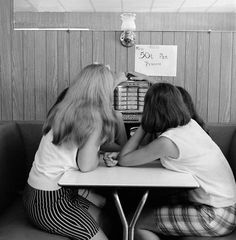 1960s Teenage girls putting coins in juke box of diner soda shop.