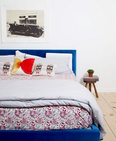 An upholstered blue bed plays like a neutral base against complementary mixed patterns.