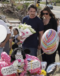 Christian Bale and his wife visit the memorial to honor shooting victims in Aurora, CO