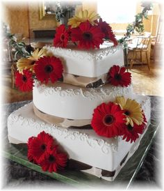 Painted fondant ribbon like camo.  Real gerbera daisies on fondant covered cake.  Creative Cakes by Patty