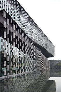 Xinjin Zhi Museum by Kengo Kuma & Associates - Cheng Du, China - The tile used for façade is made of local material and worked on in a traditional method of this region, to pay tribute to Taoism that emphasizes on nature and balance. Tile is hung and floated in the air by wire to be released from its weight (and gain lightness). Clad in breathing façade of particles, the architecture is merged into its surrounding nature.
