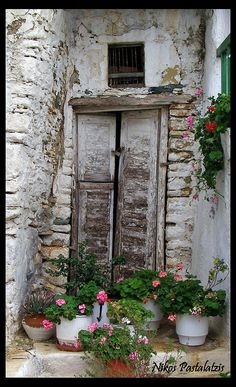 an old weathered building with pots of geraniums