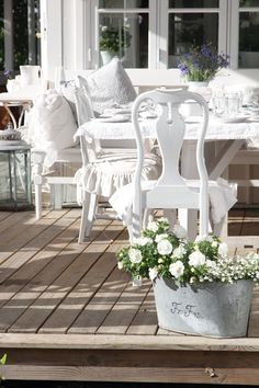 Vita drömmar & busiga barn. Love the shape of these chairs, the beautiful lavender coloured flowers and the lovely flowers in the front. Very peaceful setting