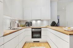 biała nowoczesna kuchnia z drewnianym blatem
