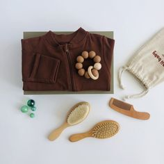 * Zip-up romper featuring integrated fold over scratch mitts and zip guard in Rust. * Baby grooming brush set includes a 100% goat hair brush and scalp massage brush in a drawstring linen bag. * Food grade silicone and beech wood bead baby teether ring in Clay. * All orders arrive beautifully gift wrapped in our Classic gift box (26x18x8cm). Re-use as a keepsake box. Romper A plain romper featuring a zip opening for easy changing morning and night, zip guard for added comfort, integrated scratch