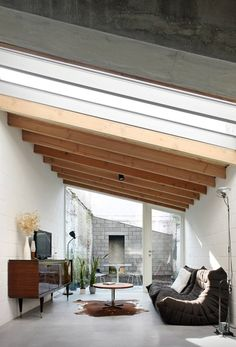 Slanted Ceiling, Exposed Wood Beams, Dark Grey Squishy Couch, Window Wall, Inner Courtyard // different