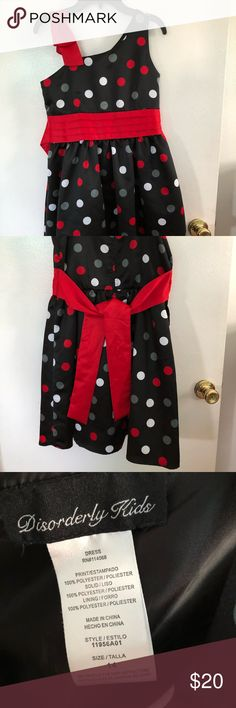 Disorderly Kids Girls Christmas Dress This is a Disorderly Kids Girls Christmas dress. It is a black dress with red, white, and grey polka dots, and a red bow on the shoulder. 100% Polyester Discovery Kids Dresses