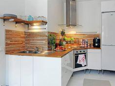 A cozinha é beneficiada pelo pé-direito alto dando destaque para a presença da coifa. Em uma cozinha compartilhada, o uso do depurador é indispensável. No projeto, os móveis não vão até o chão para facilitar a limpeza.
