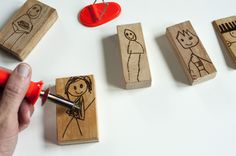 Joel uses a wood burning tool to draw his children's drawings of people onto blocks.