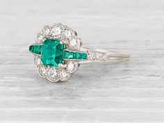 Early Art Deco Tiffany & Co engagement ring made in platinum and centered with an approximately 1.15 carat emerald cut emerald. Accented with baguette cut emeralds and old European cut diamonds. Signed Tiffany & Co. Circa 1920