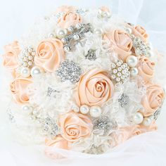 This bridal brooch bouquet is handcrafted with beautiful sparkling brooches, peach colored satin ribbon, lace flowers, and faux pearls. Unlike a flower bouquet, brooch bouquets last a lifetime and are