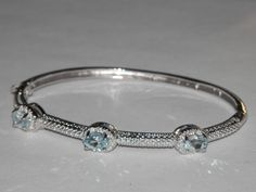 Simple, but elegant! This bracelet has 3 genuine blue topaz and is set in silver-tone mounting. The front of it has texture and the back is high polished. Closure has a safety catch and hinge opening for easy on and off.  Measures 7 inches inside circumference. Oval shaped to fit the wrist better.