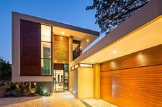 Side entrance features multiple expanses of natural wood paneling sandwiched between layers of concrete and black metal framing. Open design means we can see through to opposite end of the home.