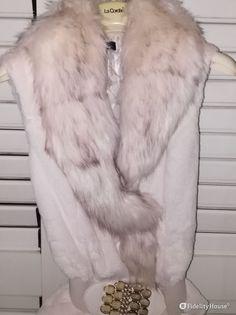 Gilet bianco in pelliccia sintetica adatto per ogni occasione, sia casual che elegante. Il gilet è impreziosito da una cintura con pietre color beige.