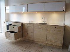 Køkkenet er i finér af fyrretræ. Bordplade af hvid ridsefri laminat. Overskabe af fyr med hvide plexiglas skydelåger.