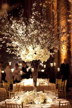 Dramatic tall wedding centerpiece with white flowers and handing candle holders