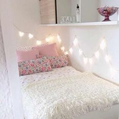 string lights above the bed, pretty floral pillows and a lacy blanket.