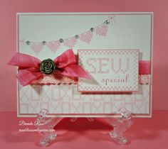 """Cross Stitch Wishes-Jan-by Brenda Rose.  Blush ink for the """"XO"""" stamp. Cotton candy ink to stamp the sentiment box, banner, and hearts. Color ready seam binding ribbon, colored with ink.  Simply use a sponge dauber and cotton candy ink to create this beautiful pink ribbon.  Piece of pink cotton lace.  Grey rose is from slate mini medley collection, and sparkles on the banner."""