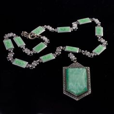 1920s-30s Art Deco necklace of green satin glass, chrome, marcasites and enamel. The glass stone of the pendant looks like satin and is bezel set on a chrome and marcasite setting. The necklace is composed of matching green enamel set in chrome inks with marcasites. spring clasp