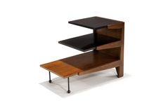 Greta Grossman Step table Glenn of California, designed c. 1952 Walnut frame and lower shelf with Thermoset Plastic upper shelves and black iron legs with round walnut tips Model No. 6226 24.25″ x 31″ x 18″ Literature:  Glenn of California