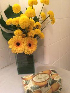 No lavabo o arranjo assimétrico de gérberas amarelas e o vaso coberto por folhagens