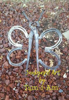 Junkyard Art by Tam-I-Am. Repurposed nippers and horse shoes become a butterfly. Has attached ground stake. Scrap metal art.