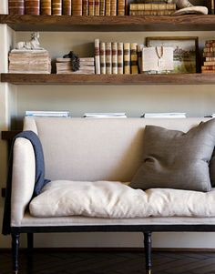 Leather bound books on floating shelves and linen settee