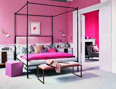 Pink is the key colour to this modern and grown up bedroom. Four poster metal bed with upholstered headboard in pale pink sits well with the cerise geometric wallpaper and deep pink eiderdown which matches the walls in the adorning dressing room creating a cohesive interior. Homes & Gardens, June 2014. Styling Claudia Bryant, photographs Jan Baldwin.