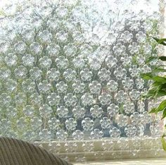 Make an outdoor privacy screen using the bottoms of water bottles... surprisingly pretty!