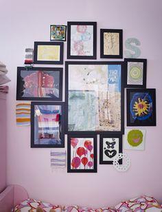 Lajitelma IKEA-kehyksiä kollaasiksi ripustettuna. Kehyksissä lapsen taideteoksia.