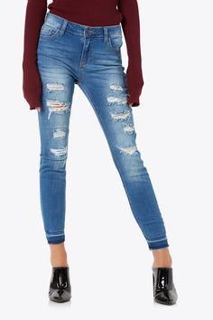 Mid rise cropped skinny jeans with distressed accents and dye coloring on hem.