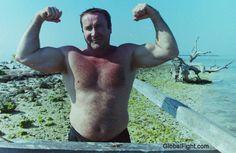 old man flexing beach
