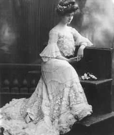 """Carroll McComas, 1905  """"Actress Carroll McComas poses for the camera in 1905. Her clothes are typical of those of the elegant woman of the time, with an abundance of lace and frills and sweeping skirt. The waist was pulled in by corsets, and the bosom flung forward, but dress bodices fell loosely, billowing slightly over the waistband at the front. This would have been an evening dress, as high-collared dresses were always worn for day."""""""