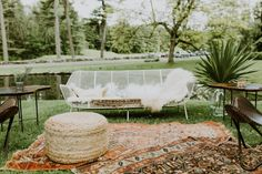 Bohemian outdoor wedding reception lounge seating with wire couch, rattan pouf, and Persian rugs| Image by Mark Spooner