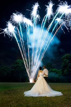 We love the symmetry of this shot, with the bride's shimmering white dress perfectly catching the blue reflections of the shimmering fireworks.