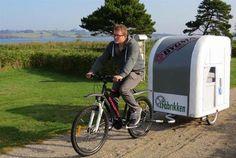 Man pulling bicycle camper