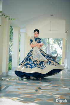 Twirling Bride - Bride in a Blue Lehenga | WedMeGood | Twirling Bride in a Blue Lehenga with Golden Embroidery and Silver Border and Net Silver Dupatta #wedmegood #Indianbride #indianwedding #blue #silver #gold #lehenga #twirling #bridal