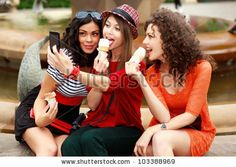 three beautiful women photographing themselves eating icecream - stock photo