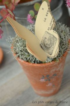 Butterfly out of book pages resting on moss in a clay pot...