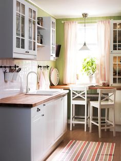bright kitchen, wooden countertops, ceramic sink, small counter with bar stools