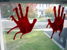"""Corn starch, red food coloring, and your handprints can make for some seriously scary décor. Simply buy thrift store paintings and smear them with your """"blood."""""""