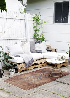 Pallet Outdoor Furniture Wood pallet couch on patio with white cushions and throw pillows. - This article will show you the steps, materials and tools you need to create an L-shaped couch using pallet wood and how to make no sew cushions. Pallet Garden Furniture, Outdoor Furniture Plans, Home Furniture, Furniture Ideas, Rustic Furniture, Antique Furniture, Furniture Online, Modern Furniture, Furniture Design